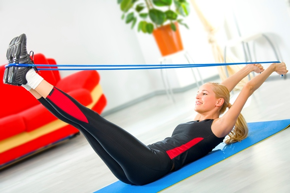 Young woman doing fitness exercises with expander at home