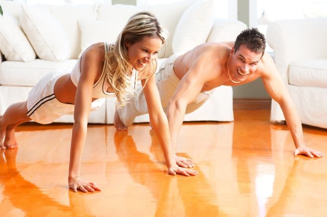 Young man and woman woman doing exercise in the sunny room